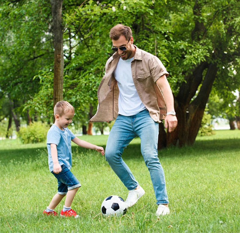 father and child playing football